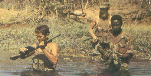 Selous Scouts cross a river during a tracking expedition.
